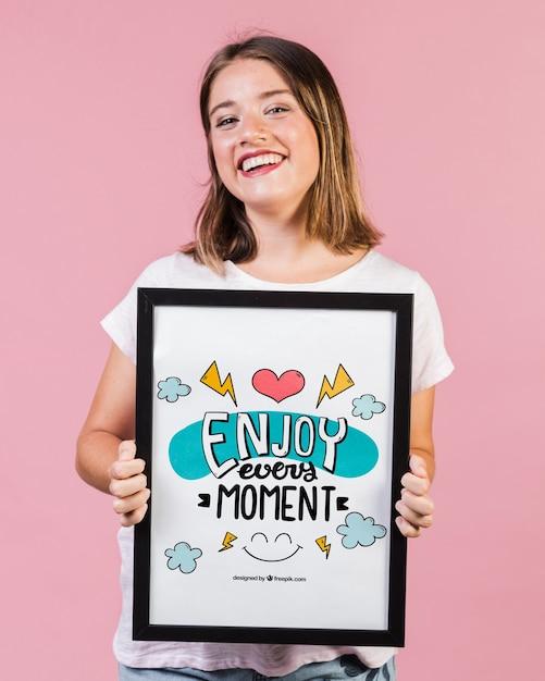 Mulher jovem sorridente, mostrando um modelo de quadro Psd grátis