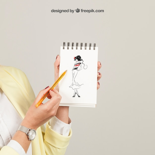 Mulher mostrando desenho no bloco de notas Psd grátis