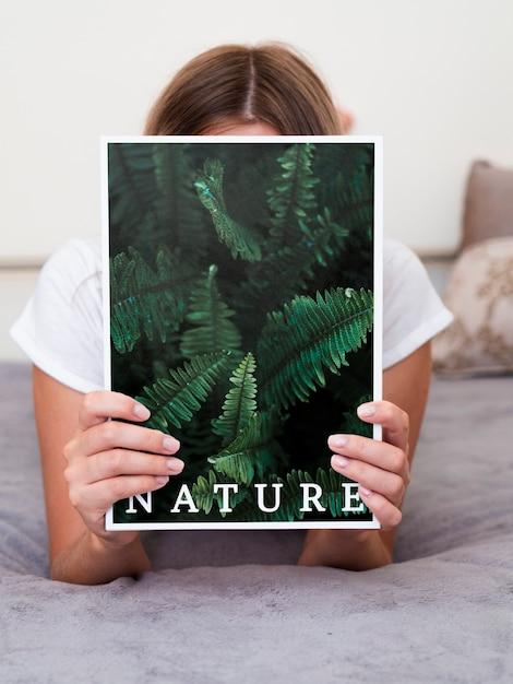 Mulher na cama segurando uma revista de natureza Psd grátis
