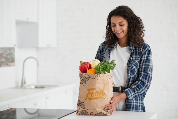 Mulher na cozinha com saco de legumes frescos Psd grátis