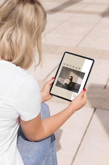 Mulher na rua lendo livro no tablet Psd grátis