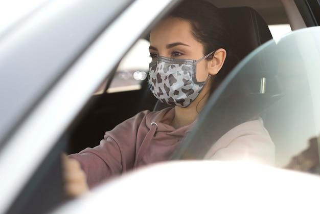Mulher no carro vestindo máscara Psd grátis