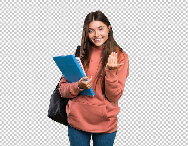 Mulher nova do estudante que guarda os cadernos que convidam para vir com mão. feliz que você veio Psd Premium