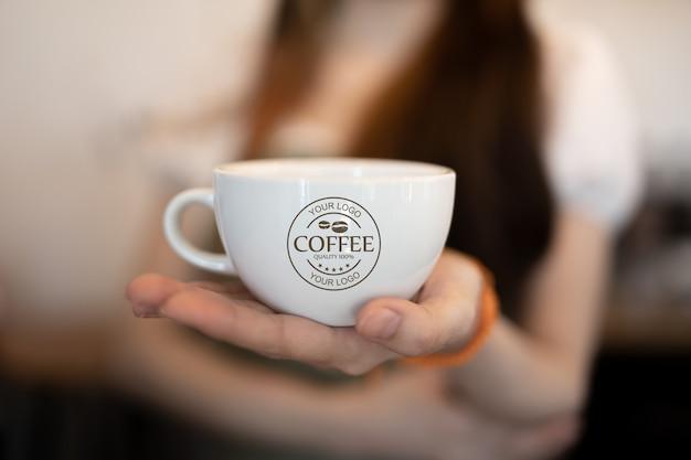 Mulher segurando a maquete da caneca de café Psd grátis