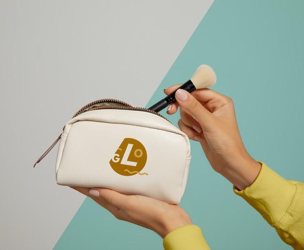 Mulher segurando bolsa de maquiagem Psd grátis