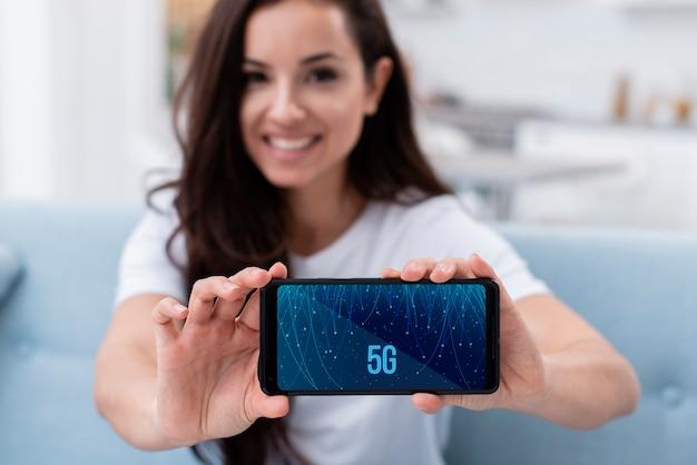 Mulher segurando um telefone com modelo de conceito 5g Psd grátis