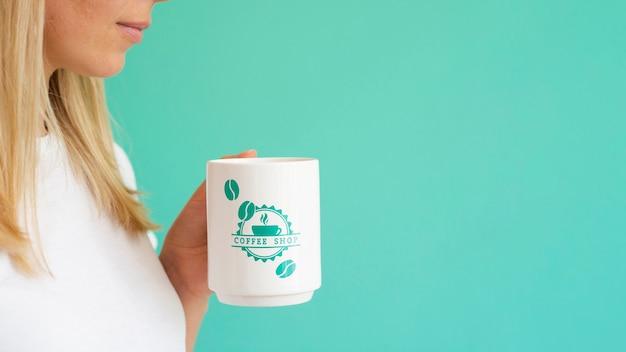Mulher segurando uma caneca de café branco com espaço de cópia Psd grátis