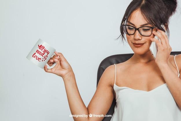 Mulher segurando uma caneca de café muck e fazendo um telefonema Psd grátis