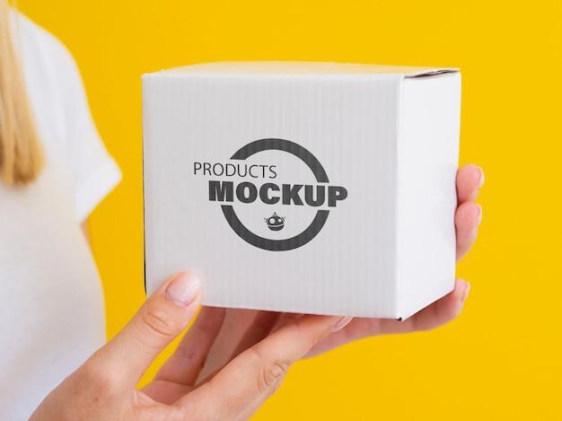 Mulher segurando uma maquete de caixa branca Psd grátis