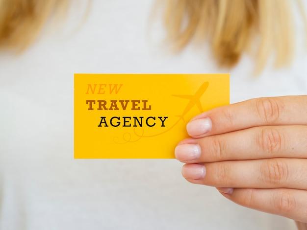 Mulher segurando uma maquete de cartão de agência de viagens Psd grátis