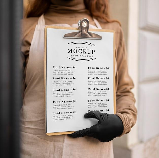 Mulher segurando uma maquete de menu de restaurante na área de transferência Psd grátis