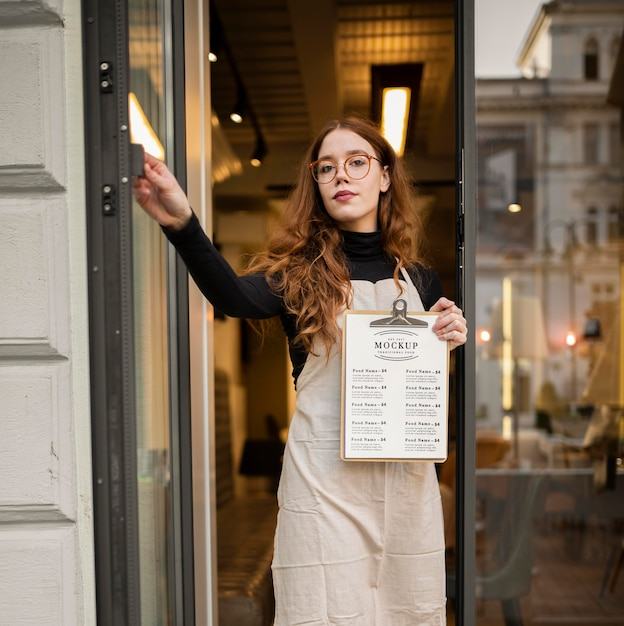 Mulher segurando uma maquete de menu de restaurante Psd grátis
