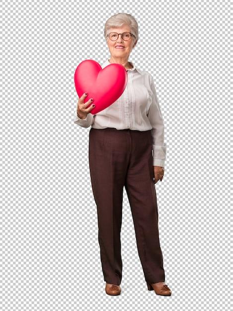 Mulher sênior de corpo inteiro alegre e confiante, oferecendo uma forma de coração para a frente, conceito de amor, companheirismo e amizade Psd Premium