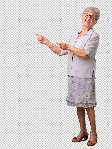 Mulher sênior de corpo inteiro, apontando para o lado, sorrindo surpreso apresentando algo Psd Premium