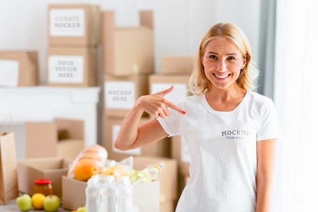 Mulher sorridente apontando para sua camiseta Psd Premium