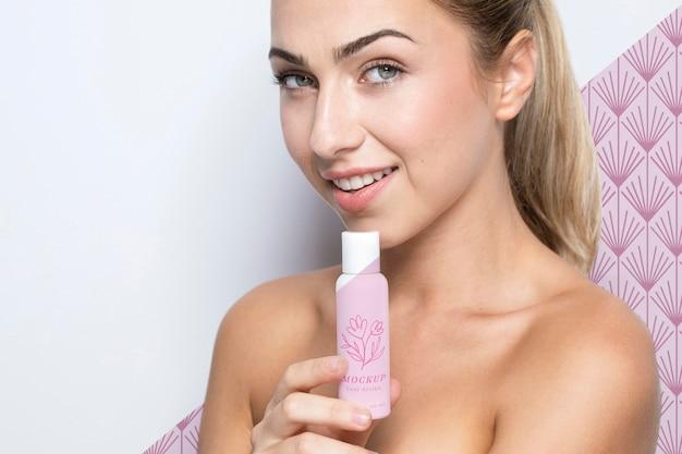 Mulher sorridente segurando uma maquete de produto para a pele Psd grátis