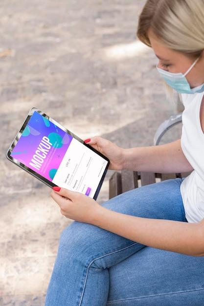 Mulher usando máscara na rua lendo livro no tablet Psd grátis