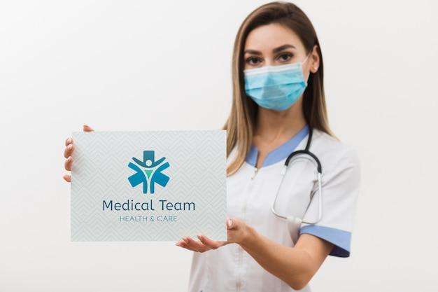 Mulher vestindo máscara médica e estetoscópio Psd Premium