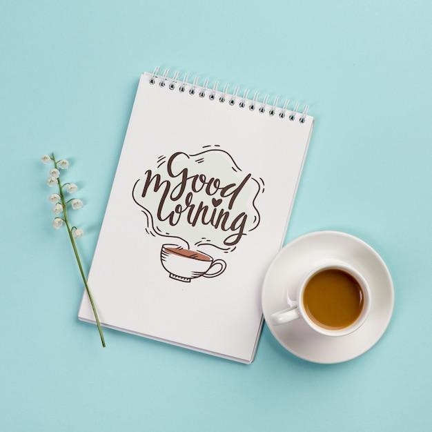 Notebook de vista superior com mensagem positiva e café Psd grátis