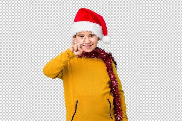 O rapaz pequeno que comemora o dia de natal que veste um chapéu de santa isolou mostrar chifres gesticula como um conceito da revolução. Psd Premium