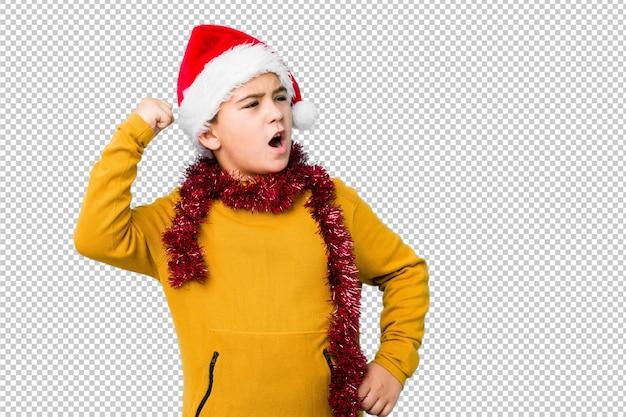 O rapaz pequeno que comemora o dia de natal que veste um chapéu de santa isolou o levantamento do punho após uma vitória, conceito do vencedor. Psd Premium