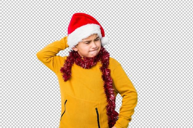 O rapaz pequeno que comemora o dia de natal que veste um chapéu de santa isolou o toque na parte de trás da cabeça, pensando e fazendo uma escolha. Psd Premium