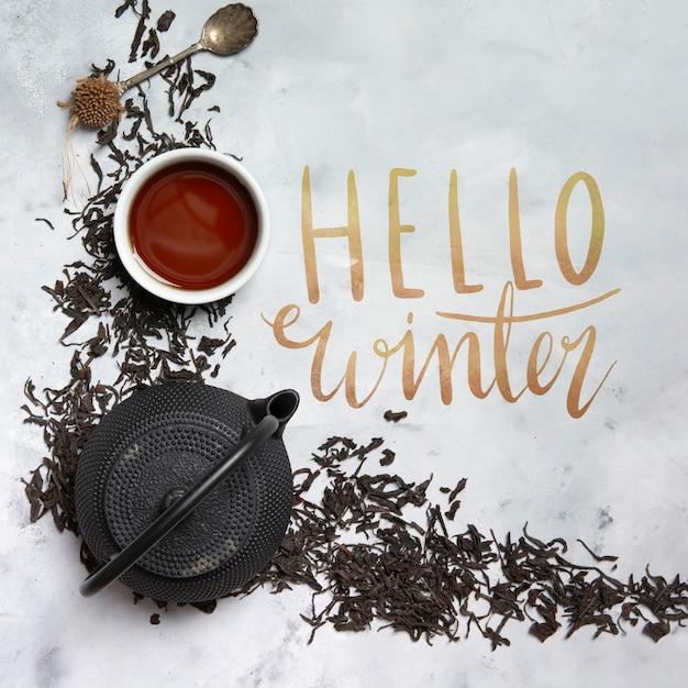 Olá mensagem de inverno ao lado de chaleira com chá Psd grátis