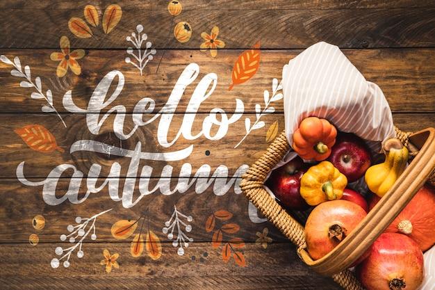 Olá outono citação com cesta de piquenique cheia de legumes Psd grátis