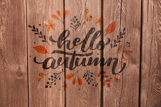 Olá outono, escrito em um fundo de madeira Psd grátis