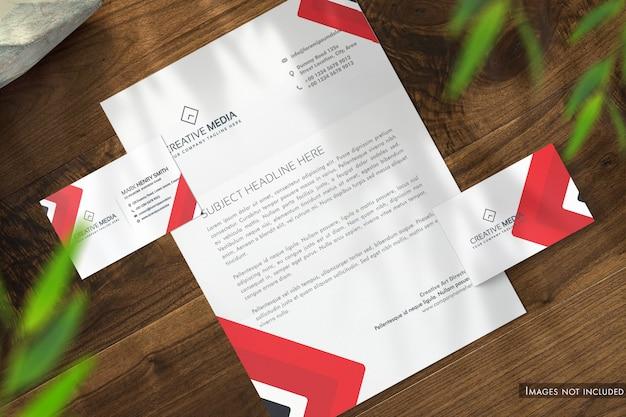 Papel timbrado e cartões de visita na mesa de madeira ver maquete Psd Premium
