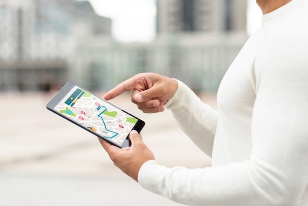 Pessoa ao ar livre, olhando no mapa de um tablet Psd grátis