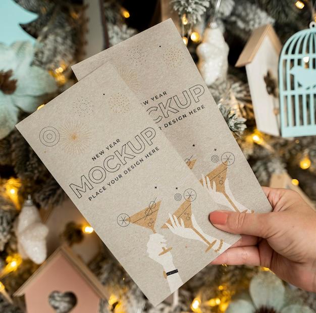 Pessoa segurando cartões mock-up na frente de decorações de natal Psd grátis