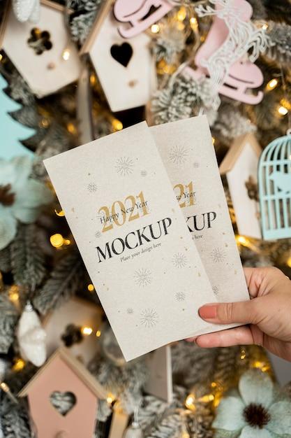 Pessoa segurando modelos de cartões de ano novo na frente de decorações de natal Psd Premium