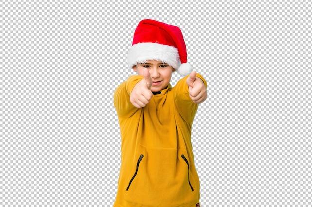 Rapaz pequeno que comemora o dia de natal que veste um chapéu de santa com polegares levanta, felicidades sobre algo, apoia e respeita o conceito. Psd Premium