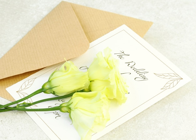 Rosas amarelas, envelope e cartão de convite em fundo cinza Psd Premium
