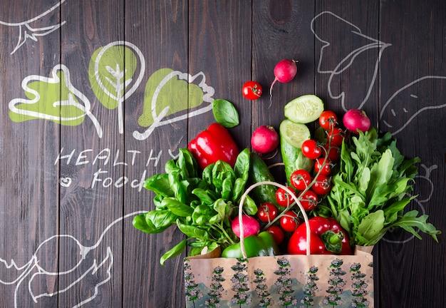 Sacola cheia de legumes em uma superfície de madeira Psd Premium