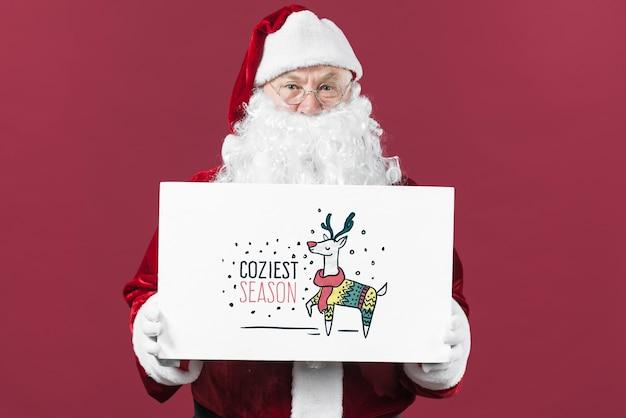 Santa apresentando maquete de placa de papel Psd grátis
