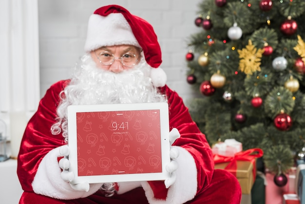 Santa apresentando maquete de tablet Psd grátis