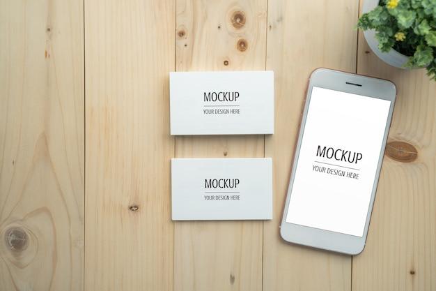 Smartphone de tela em branco branco e maquete de cartão na mesa de madeira Psd Premium