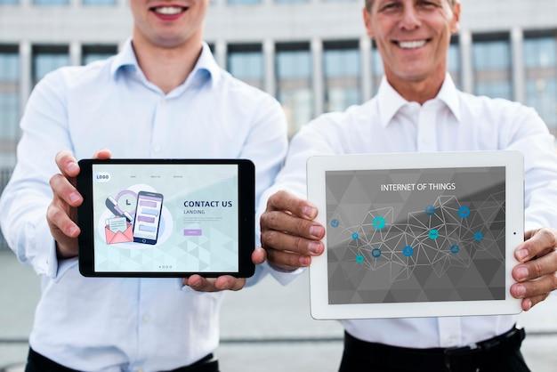 Smiley homens segurando dispositivos digitais para marketing na internet Psd grátis