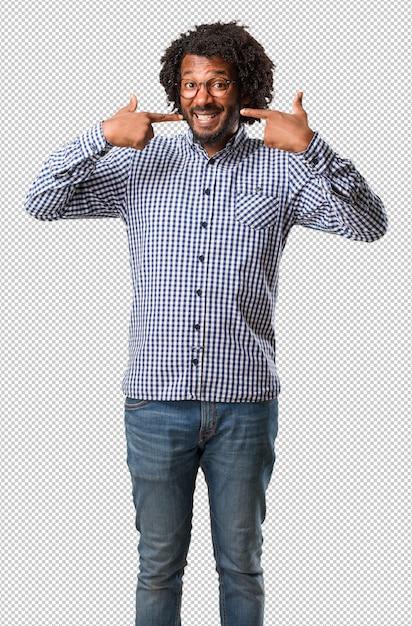 Sorrisos de homem afro-americano de negócios bonito, apontando a boca, dentes perfeitos, dentes brancos, tem uma atitude alegre e jovial Psd Premium