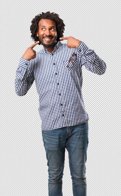 Sorrisos de homem afro-americano de negócios bonito, apontando a boca, o conceito de dentes perfeitos, dentes brancos, tem uma atitude alegre e jovial Psd Premium