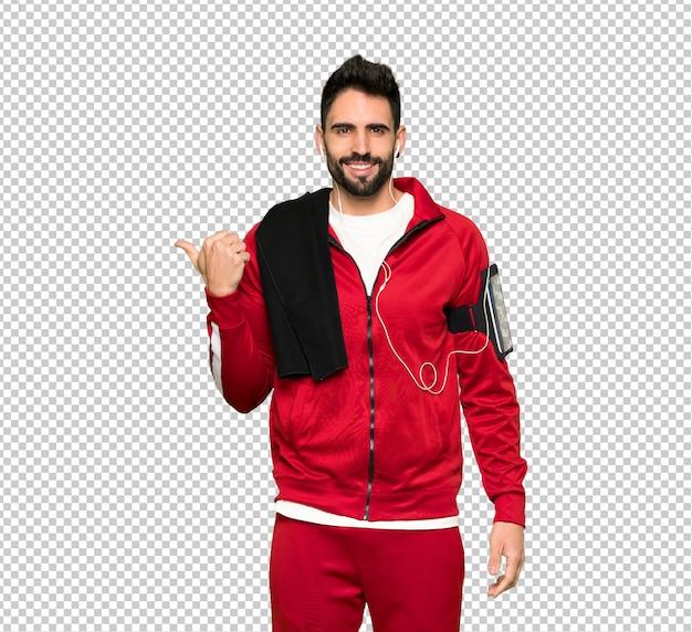 Sportman bonito apontando para o lado para apresentar um produto Psd Premium