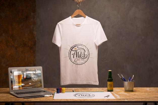 T-shirt branca vista frontal com laptop e cerveja Psd Premium