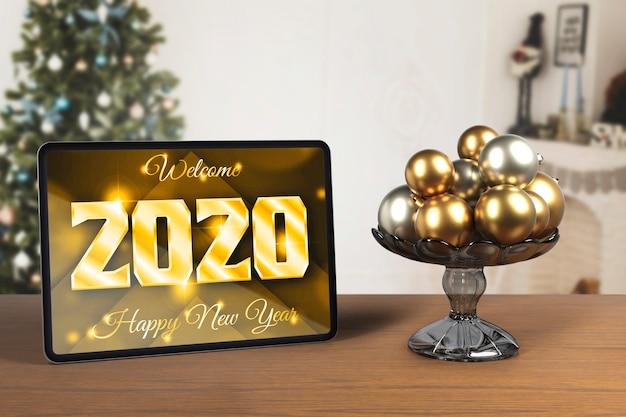 Tabuleta ao lado da bandeja com globos para o ano novo Psd grátis