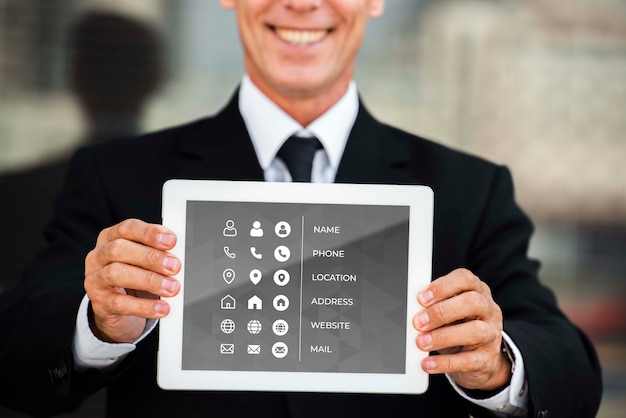 Tiro médio do homem sorridente, mostrando o tablet para fins de marketing Psd grátis