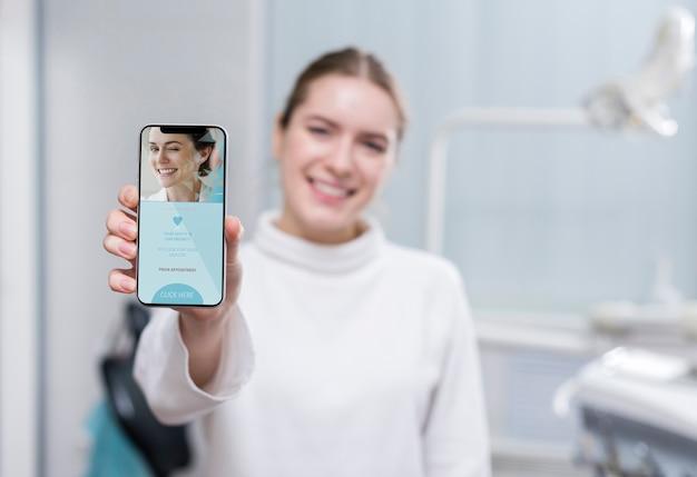 Tiro médio mulher segurando um smartphone Psd grátis