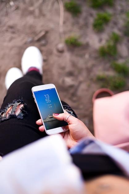 Um, mulher jovem, viajante, sentar, e, mantenha, smartphone, em, mão Psd Premium