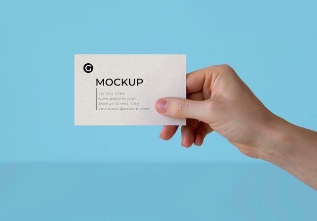 Uma mão segurando uma maquete de cartão de visita Psd grátis
