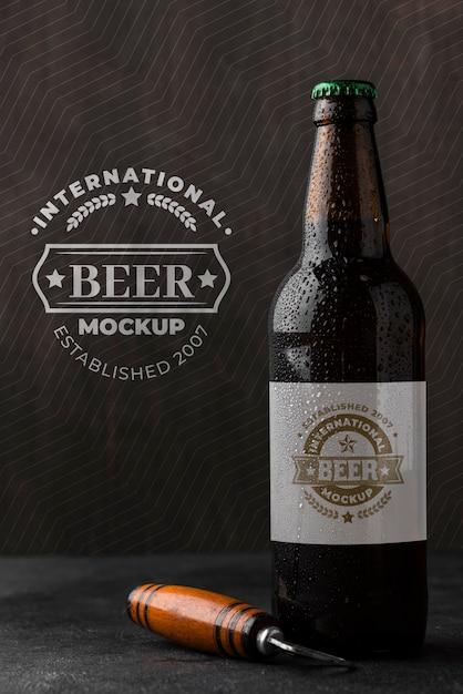 Vista frontal da garrafa de cerveja com abridor Psd Premium